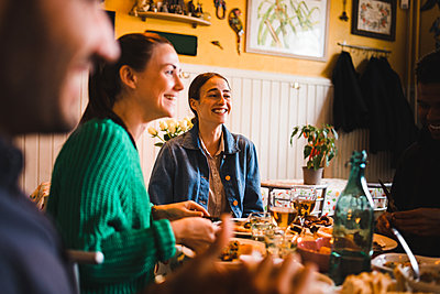 Smiling young women sitting at table in restaurant while enjoying dinner party - p426m2046345 by Maskot