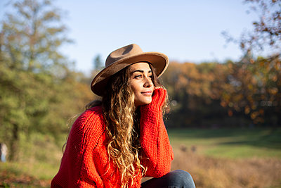 Young woman with hat day dreaming in the sunshine - p975m2222107 by Hayden Verry