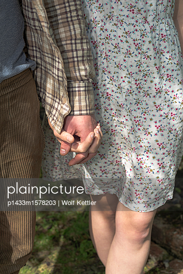 Young couple holding hands - p1433m1578203 by Wolf Kettler