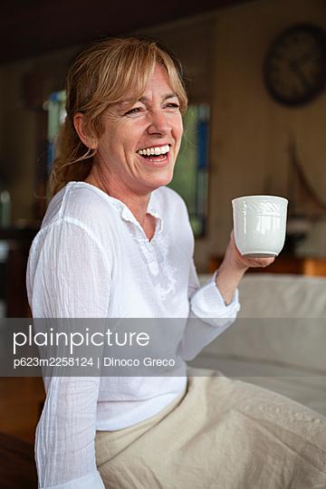 Smiling senior woman having coffee - p623m2258124 by Dinoco Greco