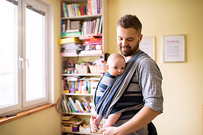 Father with baby son in sling at home - p300m1417099 by HalfPoint
