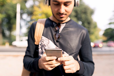 Young man with headphones and cell phone outdoors - p300m1536146 by Francesco Morandini