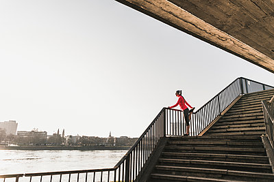Young woman stretching on stairs at a river in the city - p300m1568501 by Uwe Umstätter