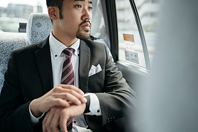 Young businessman in a taxi checking the time and looking out of window - p300m2140621 by Juri Pozzi