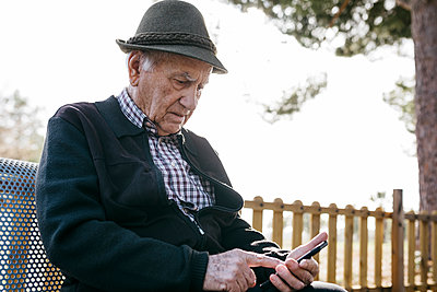Old man with, sitting on bench, using smartphone - p300m2166553 by Josep Rovirosa