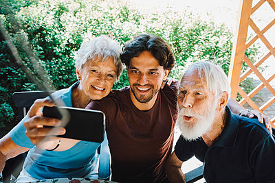 Smiling male caretaker taking selfie with senior man and woman at back yard - p426m2074402 by Maskot
