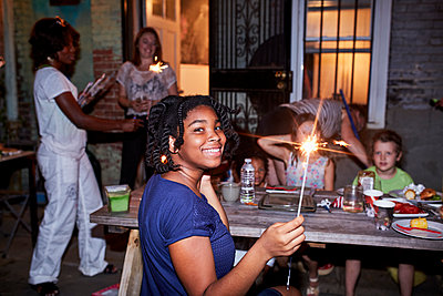 Smiling girl holding burning sparkler at backyard party - p555m1303242 by Granger Wootz