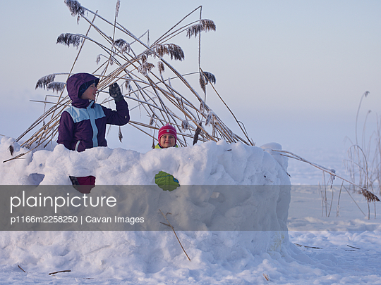 Girls playing in snow fortress on frozen lake during cold winter day - p1166m2258250 by Cavan Images