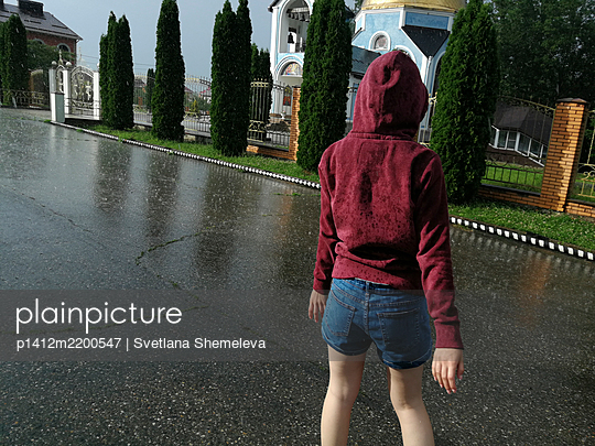 Teenage girl in hooded jacket in the summer rain - p1412m2200547 by Svetlana Shemeleva