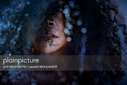 Woman with curly hair looking at camera - p1619m2192716 by Laurent MOULAGER