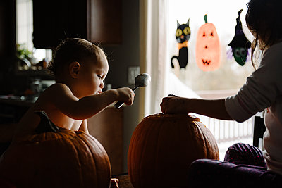 two kids Pumpkin carving at halloween in their home - p1166m2269341 by Cavan Images