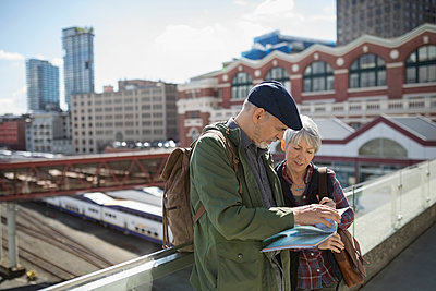 Senior couple tourists looking at maps on sunny urban rooftop - p1192m1512034 by Hero Images