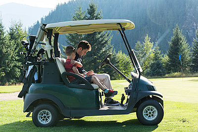 Father and son sitting in the golf cart on a sunny day - p1315m1565182 by Wavebreak