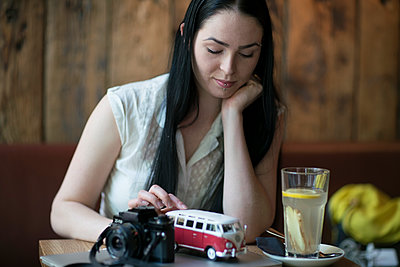 Woman in cafe with reflex camera and miniature VW bus - p1332m1540009 by Tamboly