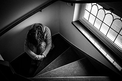Depressed woman is sitting in staircase - p1687m2284283 by Katja Kircher