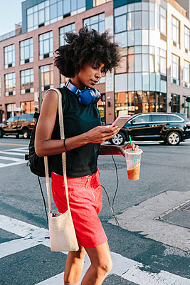 Young woman with headphones and smart phone crossong street in Brooklyn, carying take away drink - p300m1356347 by Giorgio Fochesato