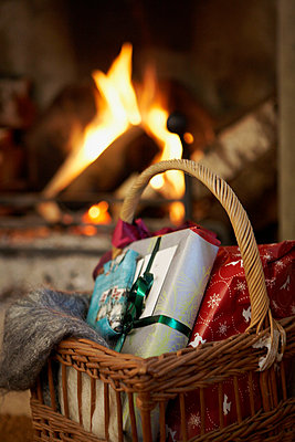 Christmas presents in basket next to open fire - p349m789717 by Brent Darby