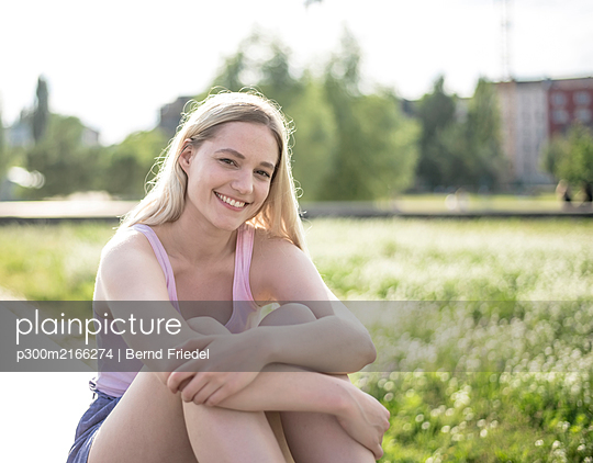 Portrait of smiling young woman in summer - p300m2166274 by Bernd Friedel