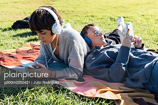 Young friends wearing headphones using smart phones while lying on blanket at park - p300m2252421 by Julio Rodriguez