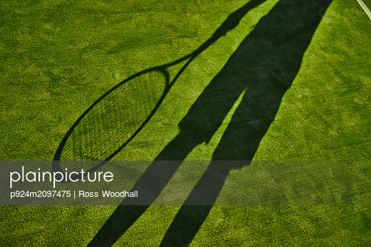 Cropped shadow of tennis player with tennis racket on green lawn - p924m2097475 by Ross Woodhall