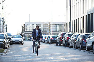 Businessman riding bike in city street - p1026m1139962 by Patrick Frost