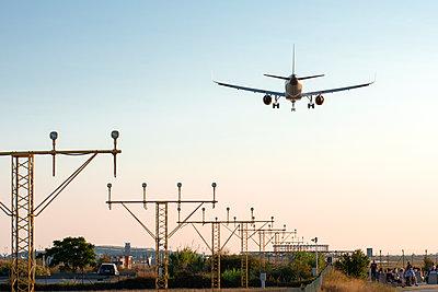 airplane landing at sunset - image - p1166m2179336 by Cavan Images