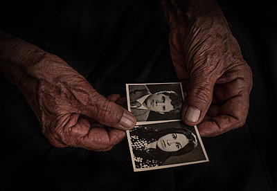 Wrinkled hands holding passport photographs in black and white  - p1508m2168822 by Mona Alikhah