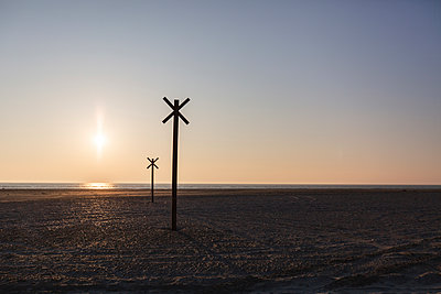 Denmark, Romo, Silhouettes of distance markers on coastal beach at sunset - p300m2180013 by Anke Scheibe