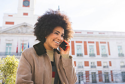 Smiling woman talking on mobile phone while standing in city - p300m2252656 by Jose Carlos Ichiro