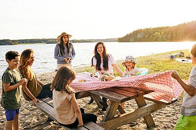 Family having picnic at lake - p312m2299487 by Plattform