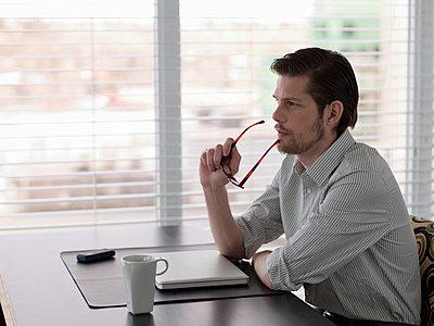 Businessman sitting at desk - p924m768333f by Dan Bannister