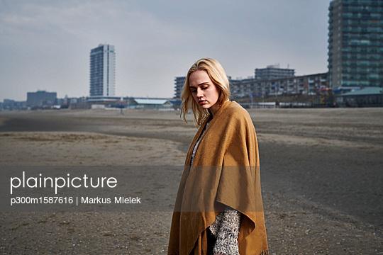 Netherlands, Zandvoort, portrait of  blond young woman on the beach wearing light brown cape - p300m1587616 von Markus Mielek