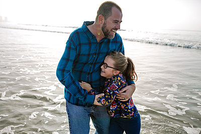 Cheerful father and daughter playing in sea at beach - p1166m1530928 by Cavan Images