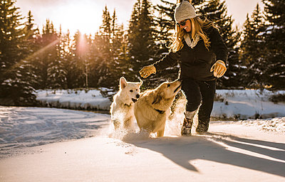 Smiling woman with dogs walking on snow covered field in forest - p1166m1532276 by Cavan Social