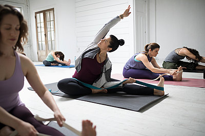 Woman practicing yoga side bend stretch with strap in yoga class - p1192m1583346 by Hero Images