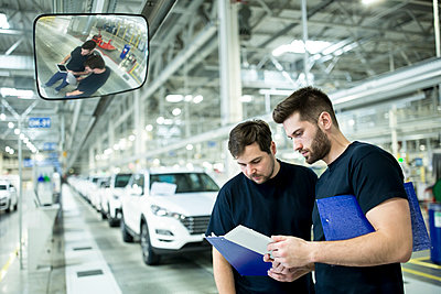 Two colleagues working in modern car factory using clipboard and tablet - p300m2246057 by Westend61