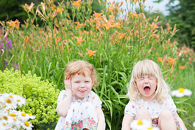 Two girls in garden fooling around - p505m1048197 by Iris Wolf