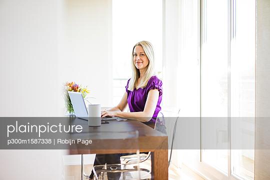 Portrait of smiling businesswoman working on laptop - p300m1587338 von Robijn Page