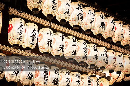 Japan, Kyoto Prefecture, Kyoto City, Rows of lanterns glowing in Japanese temple at night - p300m2154466 by Andrés Benitez