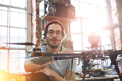 Portrait confident male designer with tattoos working on drone in workshop - p1023m1486403 by Agnieszka Olek