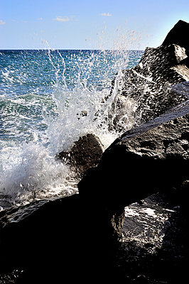 Wave crashing against black rocks - p1047m789491 by Sally Mundy
