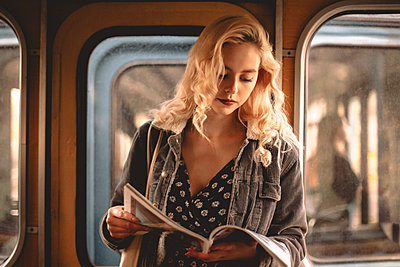Young woman reading magazine while traveling in subway train - p1166m2153500 by Cavan Images