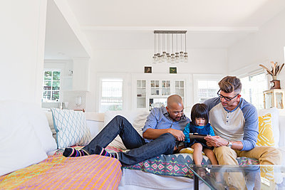 Male gay parents and adopted toddler daughter using digital tablet on living room sofa - p1192m1490747 by Hero Images