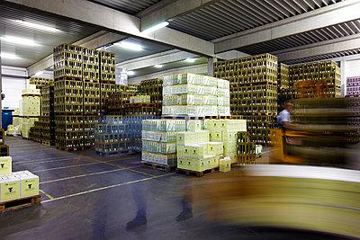 Gestapelte Kisten mit Wein in einer Lagerhalle - p1299m2231853 von Boris Schmalenberger