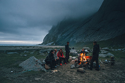Norway, Lofoten, Moskenesoy, Group of young men sitting at a campfire at Bunes Beach - p300m2005598 von Gustafsson