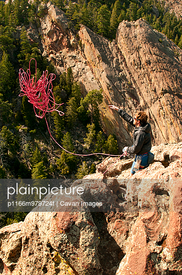 High angle view of man throwing climbing rope while standing on cliff - p1166m979724f by Cavan Images