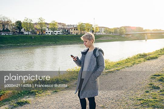 Young woman using cell phone outdoors - p300m2114059 von Francesco Buttitta