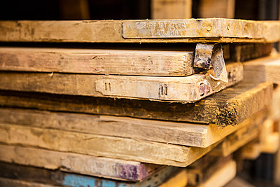 Close up of large selection of wooden planks stacked on shelves in a warehouse. - p1100m1575727 by Mint Images