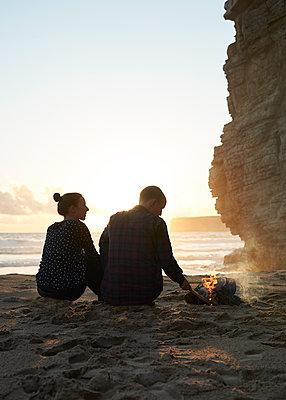 Paar macht Lagerfeuer am Strand - p1124m1112609 von Willing-Holtz