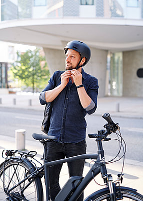 Bicycle courier puts on bike helmet - p1124m2053004 by Willing-Holtz